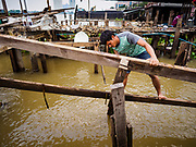 14 NOVEMBER 2017 - BANGKOK, THAILAND: Former residents of a riverside community recover lumber from their demolished homes after the city tore the homes down to make way for a 14 kilometer long (22 mile) riverfront promenade. The city also maintains that the homes interfere with navigation on the river and pose a health a safety hazard because they are prone to seasonal flooding. Thousands of families are expected to be evicted to accommodate the promenade. The riverside communities, built on stilts over the water, are prone to flooding and the city has been trying to control them for years. The houses are the only affordable housing for available to some of the poorest people in Bangkok.  PHOTO BY JACK KURTZ