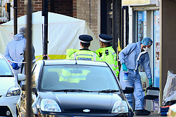 © Licensed to London News Pictures. 24/03/2019. LONDON, UK.  Forensics officers and police at off licence at Marsh Road, Pinner, north west London, after being called at approximately 06:00hrs on 24 March to reports of a man found suffering injuries from a reported stabbing.  He was pronounced dead at the scene by officers and London Ambulance Service.  Enquiries are ongoing, no arrests have yet been made.  Photo credit: Stephen Chung/LNP