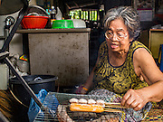 13 AUGUST 2016 - BANGKOK, THAILAND: A woman grills Thai sausages and pork balls in her home in the Pom Mahakan slum. Residents of the slum have been told they must leave the fort and that their community will be torn down. The community is known for fireworks, fighting cocks and bird cages. Mahakan Fort was built in 1783 during the reign of Siamese King Rama I. It was one of 14 fortresses designed to protect Bangkok from foreign invaders. Only of two are remaining, the others have been torn down. A community developed in the fort when people started building houses and moving into it during the reign of King Rama V (1868-1910). The land was expropriated by Bangkok city government in 1992, but the people living in the fort refused to move. In 2004 courts ruled against the residents and said the city could take the land. Eviction notices have been posted in the community but most residents have refused to move. Residents think Bangkok city officials will start evictions around August 15, but there has not been any official word from the city.      PHOTO BY JACK KURTZ