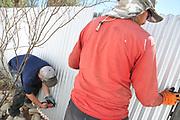 Installing fence panels along the eastern edge of my back yard.