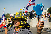 """09 DECEMBER 2013 - BANGKOK, THAILAND:  Thai anti-government protestor in front of Government House in Bangkok. Thai Prime Minister Yingluck Shinawatra announced she would dissolve the lower house of the Parliament and call new elections in the face of ongoing anti-government protests in Bangkok. Hundreds of thousands of people flocked to Government House, the office of the Prime Minister, Monday to celebrate the collapse of the government after Yingluck made her announcement. Former Deputy Prime Minister Suthep Thaugsuban, the organizer of the protests, said the protests would continue until the """"Thaksin influence is uprooted from Thailand."""" There were no reports of violence in the protests Monday.     PHOTO BY JACK KURTZ"""