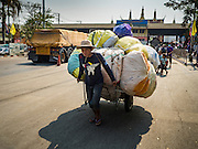 "15 FEBRUARY 2016 - ARANYAPRATHET, SA KAEO, THAILAND: A Cambodian porter in Aranyaprathet brings a load of textiles from the Cambodian side of the border into Thailand. Thais selling bottled water in the border town of Aranyaprathet, opposite Poipet, Cambodia, have reported a surge in sales recently. Cambodian officials told their Thai counterparts that because of the 2016 drought, which is affecting Thailand and Cambodia, there have been spot shortages of drinking water near the Thai-Cambodian and that ""water shortages in Cambodia had prompted people to hoard drinking water from Thailand.""     PHOTO BY JACK KURTZ"
