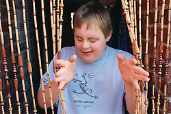 Teenage boy with Downs Syndrome parting beaded curtain,