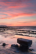 The rocky Kilve Beach, just after sunset in late summer, with pink clouds and some rocks in the foreground, which resemble a stone table.