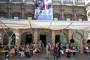 People sitting outside the entrance to the Royal Academy for the Summer Show in London, United Kingdom. The Summer Exhibition is an open art exhibition held annually by the Royal Academy in Burlington House, Piccadilly in central London, England, during the months of June, July, and August. The exhibition includes paintings, prints, drawings, sculpture, architectural designs and models, and is the largest and most popular open exhibition in the UK. It is also the longest continuously staged exibition of contemporary art in the world.