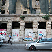 MOSTAR, BOSNIA AND HERZEGOVINA - JUNE 28:  A Police man walks in front of a building damaged by bulletts from the 1993 war on June 28, 2013 in Mostar, Bosnia and Herzegovina. The Siege of Mostar reached its peak and more cruent time during 1993. Initially, it involved the Croatian Defence Council (HVO) and the 4th Corps of the ARBiH fighting against the Yugoslav People's Army (JNA) later Croats and Muslim Bosnian began to fight amongst each other, it ended with Bosnia and Herzegovina declaring independence from Yugoslavia.  (Photo by Marco Secchi/Getty Images)