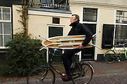Fotograaf Rob Huibers fietst met een strijkplank onder zijn arm door de Loeff Berchmakerstraat in Utrecht