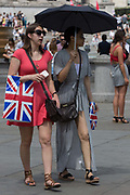 Two young women walk through Trafalgar Square carrying Union Jack shopping bags, on 13th July 2018, in London, England.
