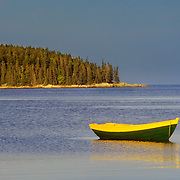 A small yellow and green dory on its mooring in Penobscot Bay.