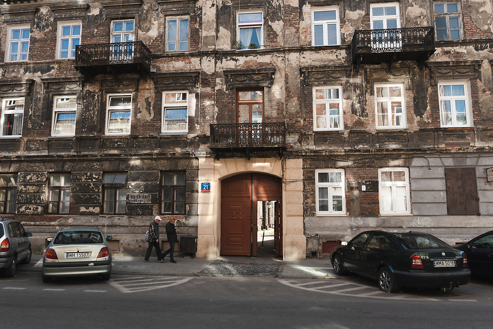 Pedestrians walk past an apartment building in the Praga district in Warsaw, Poland. (2015)