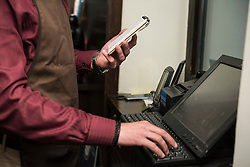Midsection of owner holding note pad in one hand and typing on computer