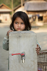 Sy 6yrs old in grade 2 at school hangs around tap stand playing with her friends. SCI has installed a gravity flow water system here. Children ften collect water for the family, and originally would have had to go down to the river with heavy buckets. Naluang Village, Nambac District, Luang Prabang Province. Lao PDR