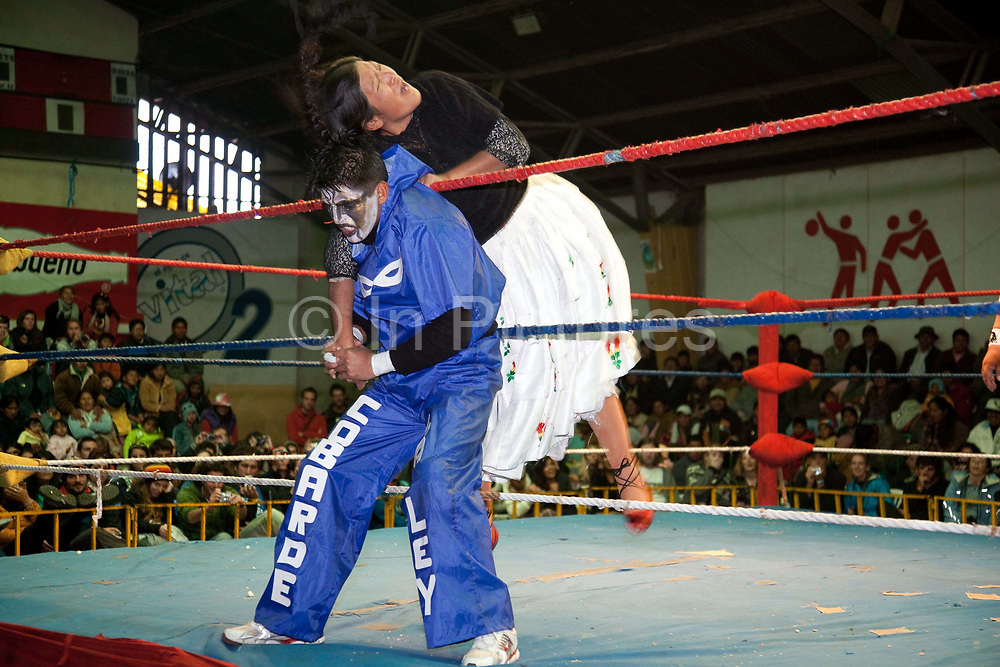 Male and female wrestlers in arm lock on ropes. Lucha Libre wrestling origniated in Mexico, but is popular in other latin Amercian countries, including in La Paz / El Alto, Bolivia. Male and female fighters participate in the theatrical staged fights to an adoring crowd of locals and foreigners alike.