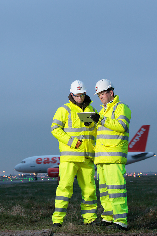 Bechtel engineers at work using iPad augmented reality software during the resurfacing of Gatwick airports runway, UK.