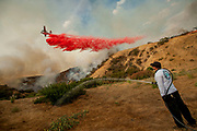 As a firefighting plane makes a drop in an effort to contain the La Tuna Canyon brush fire, Aaron Funk waters down the hillside trying to protect his parents' home near Petaluma Dr. in Sun Valley, CA. The brush fire consumed over 7000 acres.