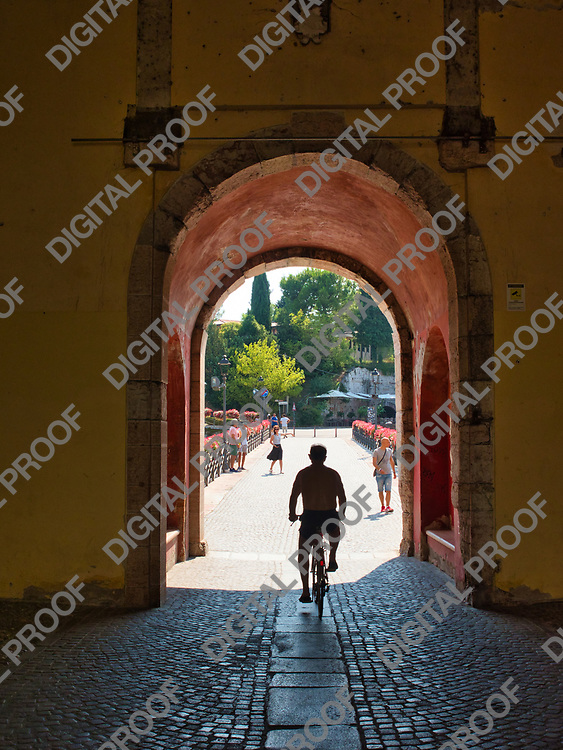 A person on a bicycle leaves the village of Peschiera del Garda on Lake Garda, Italy, passing through the arch of Porta Brescia on a sunny summer afternoon