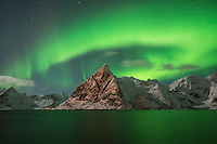 Aurora Borealis - Northern Lights fill sky over Olstind mountain peak and reflect in fjord, Toppøya, Lofoten Islands, Norway