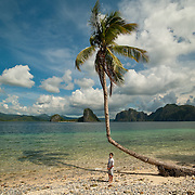 Boy and Palm tree on tropical beach in ElNido, Palawan, Philippines