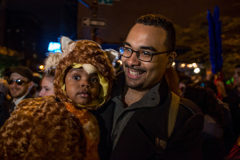 New York, NY - 31 October 2015. A father carries his child, who is dressed as a furry animal, in the Greenwich Village Halloween Parade. Because Halloween fell on a Saturday, there were more children than usual in the parade.
