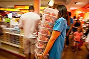 Des jeunes saisonniers déchargent des cartons de bonbons  et remplissent les rayons dans un rythme effrainé afin de faire face à la demande des clients. 4 tonnes de confiseries par jour en été. Magazin du Musee du bonbon Haribo a Uzes dans le Gard, France.