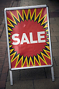 Close up of street shop Sale poster standing on pavement