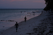 Crowd of filipinos chill out along a beach at dusk. Panglao Island, Central Visayas, Philippines, Southeast Asia