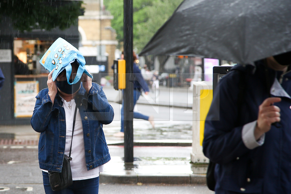 © Licensed to London News Pictures. 08/07/2021. London, UK. A woman is caught in the rain in London. According to The Met Office, more rain is expected over the next few days across London and the South East of England, with the hot weather returning later this month. Photo credit: Dinendra Haria/LNP