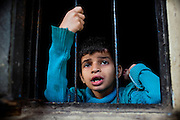 From the room she is relegated to during the day, Rachi, 7, a disabled girl affected by microcephaly and myoclonic epilepsy, is looking out onto the street in Bhopal, central India. During the day, Ranchi is restrained with a cord to her ankle, in order to prevent her from wandering off alone and being at risk of danger and abuse.