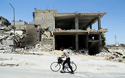 (170729) -- ALEPPO (SYRIA), July 29, 2017 (Xinhua) -- A man drags his bicycle in the shattered Ansari neighborhood, east of Aleppo city, northern Syria, July 28, 2017. The rebels had stayed in the east of Aleppo for five years before they evacuated in December of 2016. Seven months after the Syrian army took full control over the city, life starts to beat again through devastation and destruction in the area. (Xinhua/Ammar Safarjalani) (zjy) (Photo by Xinhua/Sipa USA)