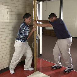 Austin,Texas 27SEP00: Junior High Science:  Hispanic 8th graders at Kealing Junior High School in Austin, TX demonstrate laws of physics by pushing in opposite directions on a door.  The heavier person should be able to stop the actions of the lighter person pushing because of his weight.  Photo by Bob Daemmrich, Inc.