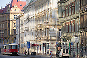 Reflected light from a nearby plate glass building, illuminates older era architecture and a city tram on Dukelskych hrdinu street, Holesovice district, Prague 7, on 19th March, 2018, in Prague, the Czech Republic.