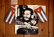 Photo of Fidel Castro pinned to the wall of a house with the Cuban flag, June 1984, in the village of Pico Turquino, Sierra Maestra Mountains.<br /> Fidel Alejandro Castro Ruz was a Cuban revolutionary and politician who governed the Republic of Cuba as Prime Minister from 1959 to 1976 and then as President from 1976 to 2008. He was loved by most of the people as a champion of socialism and anti-imperialism whose revolutionary regime advanced economic and social justice while securing Cubas independence from American imperialism.