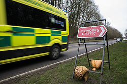 Wendover, UK. 18th March, 2021. An ambulance passes a sign indicating the location of works including the demolition of a large residential house and the felling of woodland for the HS2 high-speed rail link.
