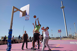 """© Licensed to London News Pictures.29/03/2021. Brighton,UK. Members of the public enjoy playing basketball during spring weather in Brighton, East Sussex. From today (Monday), the """"Stay at Home"""" advice ends with people being allowed to meet up within the 'rule of six'. Photo credit: Marcin Nowak/LNP"""