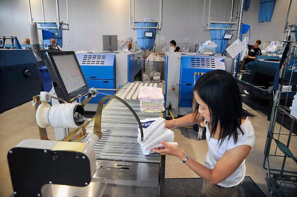 Nederland, Ooij, 4-8-2008Wasserij Verweij/Newasco. Mannen en vrouwen verwerken de was, staan aan een strijkmachine.Foto: Flip Franssen/Hollandse Hoogte