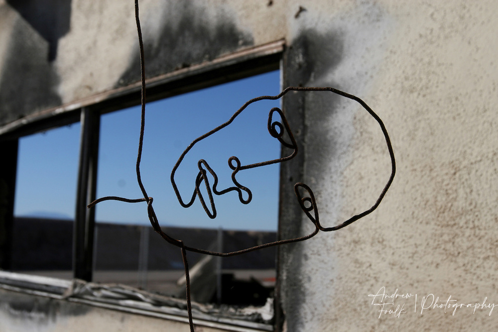Wire hanging from the roof of an abandoned house in Bombay Beach has been transformed into in eire looking face.