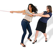 Two woman pulling a rope together on white background