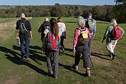 A group of country walkers stride along grassy footpath, on 21st October 2018, near Hollingbourne, Kent, England.
