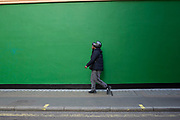 Street Scene of people passing by a green painted wall on in Soho, London, England, United Kingdom. The simplicity of the scene helps highlight the figures of ordinary people going about their daily lives. Man with a motorcycle helmet half on and half off his head.
