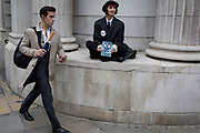 City businessmen and financiers walk through Bank as environmental activists protest about Climate Change during the blockade outside the Bank of England in the heart of the capital's financial district, the City of London aka the Square Mile, on the seventh day of a two-week prolonged worldwide protest by members of Extinction Rebellion, on 14th October 2019, in London, England.