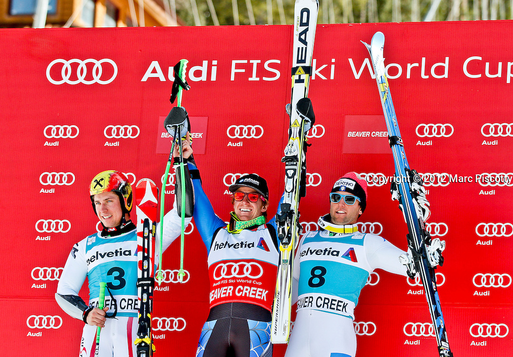 SHOT 12/2/12 2:44:13 PM - U.S. skier Ted Ligety (center) celebrates on the podium with second place finished Marcel Hirscher (left) of Austria and third place finisher Davide Simoncelli (right) of Italy after  the Birds of Prey Men's Giant Slalom race at Beaver Creek Ski Resort in Beaver Creek, Co. on Sunday December 2, 2012. Ligety won the event with a total time of 2:25.59. (Photo by Marc Piscotty / © 2012)