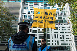 © Licensed to London News Pictures. 26/10/2021. LONDON, UK.  Police look on as activists from Animal Rebellion, a sister group to Extinction Rebellion (XR) stage a protest ahead of the upcoming UN Climate Change Conference of the Parties (COP26) taking place in Glasgow, by climbing onto the side of the Home Office building in Westminster and unfurling a banner.  Photo credit: Stephen Chung/LNP