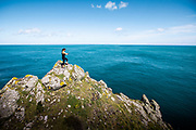 Woman out for a run on the cliff paths and stopping on  top of the rocks, surrounded by the sea, to check her Fitbit stats in Jersey, CI