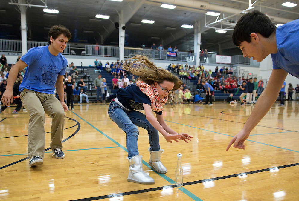 Sixth-grader Kennedi Henke reaches to knock a ping-pong ball from a bottle after spinning herself around a bat several times during the annual Christmas Cheer games Friday at Central Catholic School in Grand Island. (Independent/Matt Dixon)