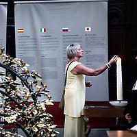 Nederland, Amsterdam , 24 juli 2014.<br /> Open Kerken.<br /> Open kerken (donderdag)<br /> Ongeveer 50 kerken in Amsterdam en omgeving luiden ook donderdagavond (24 juli) om 20.00 uur de klokken voor de slachtoffers en nabestaanden van de vliegramp in Oekraïne. Zij openen die avond de deuren zodat mensen die daar behoefte aan hebben een kaarsje kunnen aansteken of een boodschap achterlaten. De gemeente vindt het mooi dat er, een week na de ramp, plekken zijn in de stad waar Amsterdammers kunnen samenkomen om hun verdriet te delen. Vanuit de gemeente Amsterdam zullen er op diverse locaties vertegenwoordigers zijn.<br /> Op de foto: Mensen branden een kaarsje in de Westerkerk.<br /> Foto:Jean-Pierre Jans