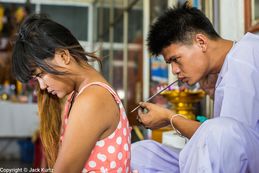 """22 MARCH 2013 - NAKHON CHAI SI, NAKHON PATHOM, THAILAND: A woman gets a sacred Sak Yant tattoo at Wat Bang Phra. Wat Bang Phra is the best known """"Sak Yant"""" tattoo temple in Thailand. It's located in Nakhon Pathom province, about 40 miles from Bangkok. The tattoos are given with hollow stainless steel needles and are thought to possess magical powers of protection. The tattoos, which are given by Buddhist monks, are popular with soldiers, policeman and gangsters, people who generally live in harm's way. The tattoo must be activated to remain powerful and the annual Wai Khru Ceremony (tattoo festival) at the temple draws thousands of devotees who come to the temple to activate or renew the tattoos. People go into trance like states and then assume the personality of their tattoo, so people with tiger tattoos assume the personality of a tiger, people with monkey tattoos take on the personality of a monkey and so on. In recent years the tattoo festival has become popular with tourists who make the trip to Nakorn Pathom province to see a side of """"exotic"""" Thailand. The 2013 tattoo festival was on March 23.    PHOTO BY JACK KURTZ"""
