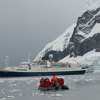 Tourists return in a zodiac raft to the National Geographic Endeavor after visiting Neko Harbor, Antarctica.