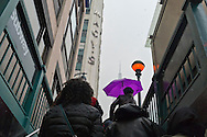 March 16, 2013 - New York, NY, U.S. - People walking up the Penn Station subway exit, with one holding purple umbrella in the snow, and with Empire State Building in backgroun, on day of the 252nd annual NYC St. Patrick's Day Parade.