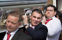© Licensed to London News Pictures. 21/04/2018. Cobham, UK. Paddy Doherty (C), and his brothers carry the coffin of their mother Queenie, Elizabeth Doherty from Sacred Heart Church in Cobham, Surrey. Elizabeth Doherty, whose son Paddy Doherty is known for appearing on My Big Fat Gypsy Wedding and winning Celebrity Big Brother 8, died of a heart attack earlier this month. Paddy Doherty claimed his mother has died of a 'broken heart' following the death of her husband almost a year ago. Photo credit: Peter Macdiarmid/LNP