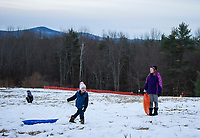 As the sun goes down Jon Dutchka takes one more run down the sledding hill at Prescott Farm Environmental Center during the Winter Solstice celebration on Saturday afternoon.  (Karen Bobotas/for the Laconia Daily Sun)